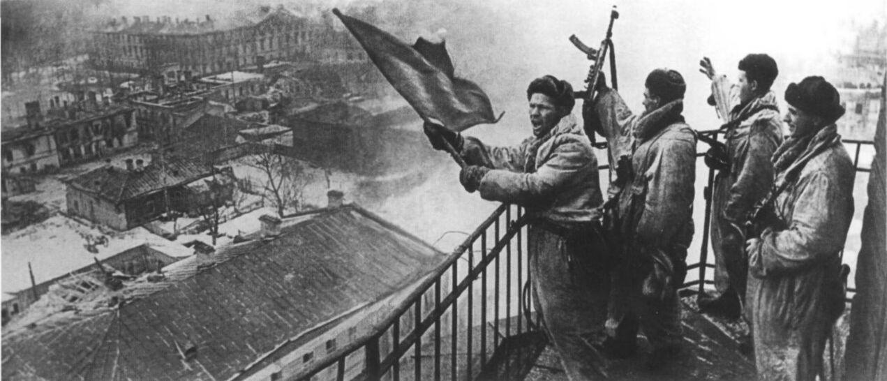 Советские солдаты поднимают красный флаг над освобожденной Гатчиной, 26 января 1944 года.